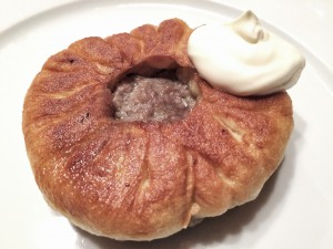 Belyashi filled with minced meat, fried in oil and served with vegetable broth or sour cream