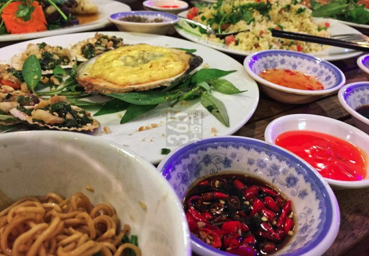 Plenty of dishes at dinner in a Saigon sidewalk bistro